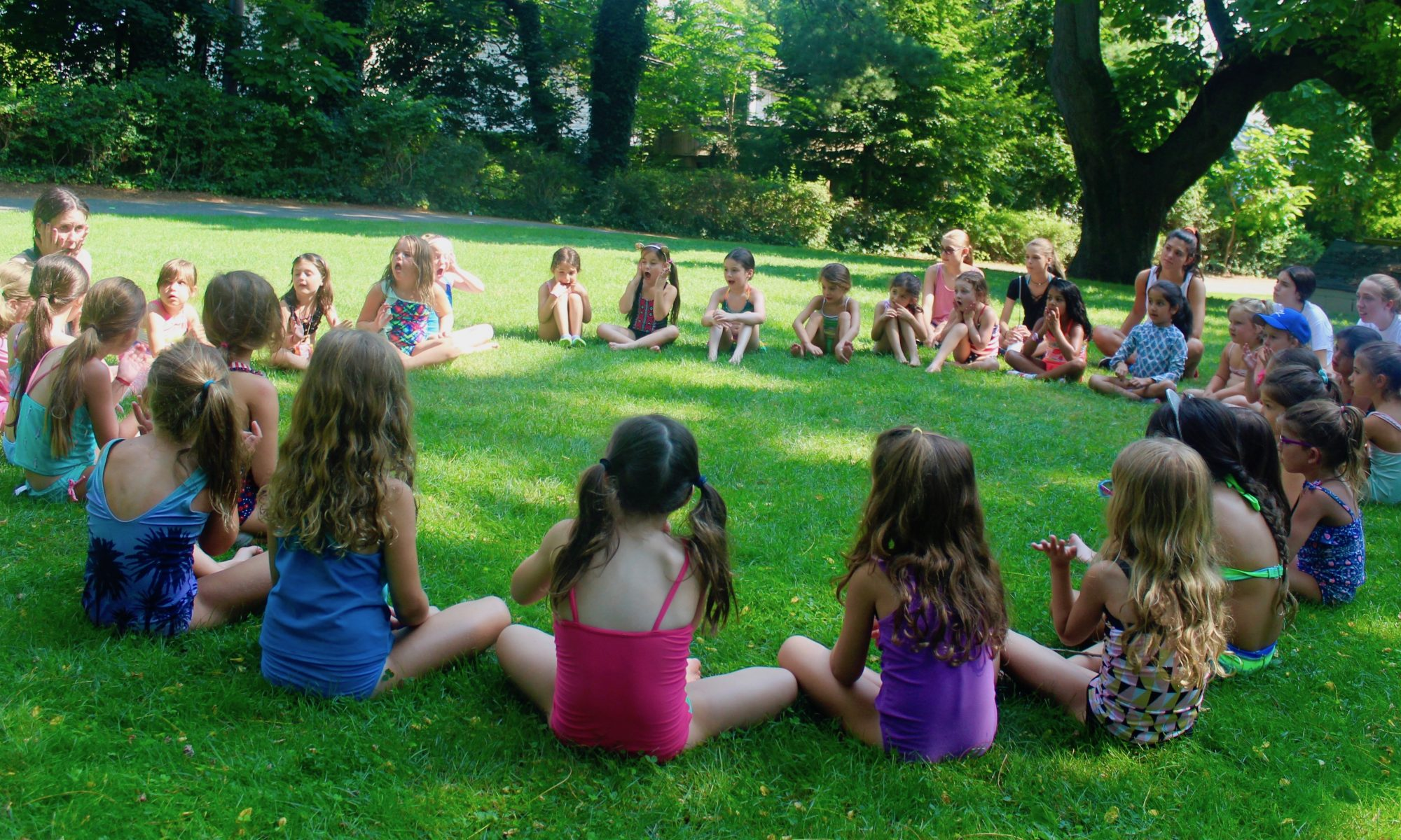 Junior camp girls in bathing suits sitting in a circle on the grass